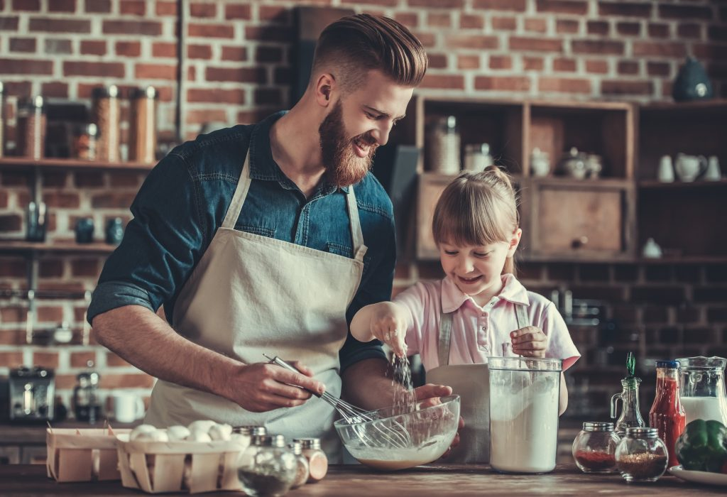 Cute little girl and her handsome bearded dad in aprons are whisking eggs, adding flour and smiling while cooking in kitchen